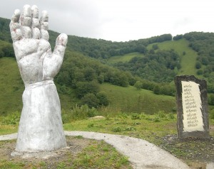 To the right of the sculpture the slab lists 12 Basque words: eskertu (to thank), eskaini (to give), eskatu (to ask for), eskuratu (to take charge of) … all connected with the word for hand – esku.
